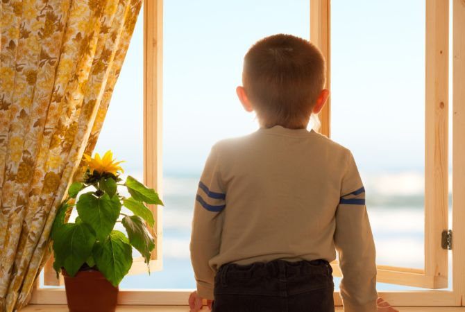 Young boy standing near an open window