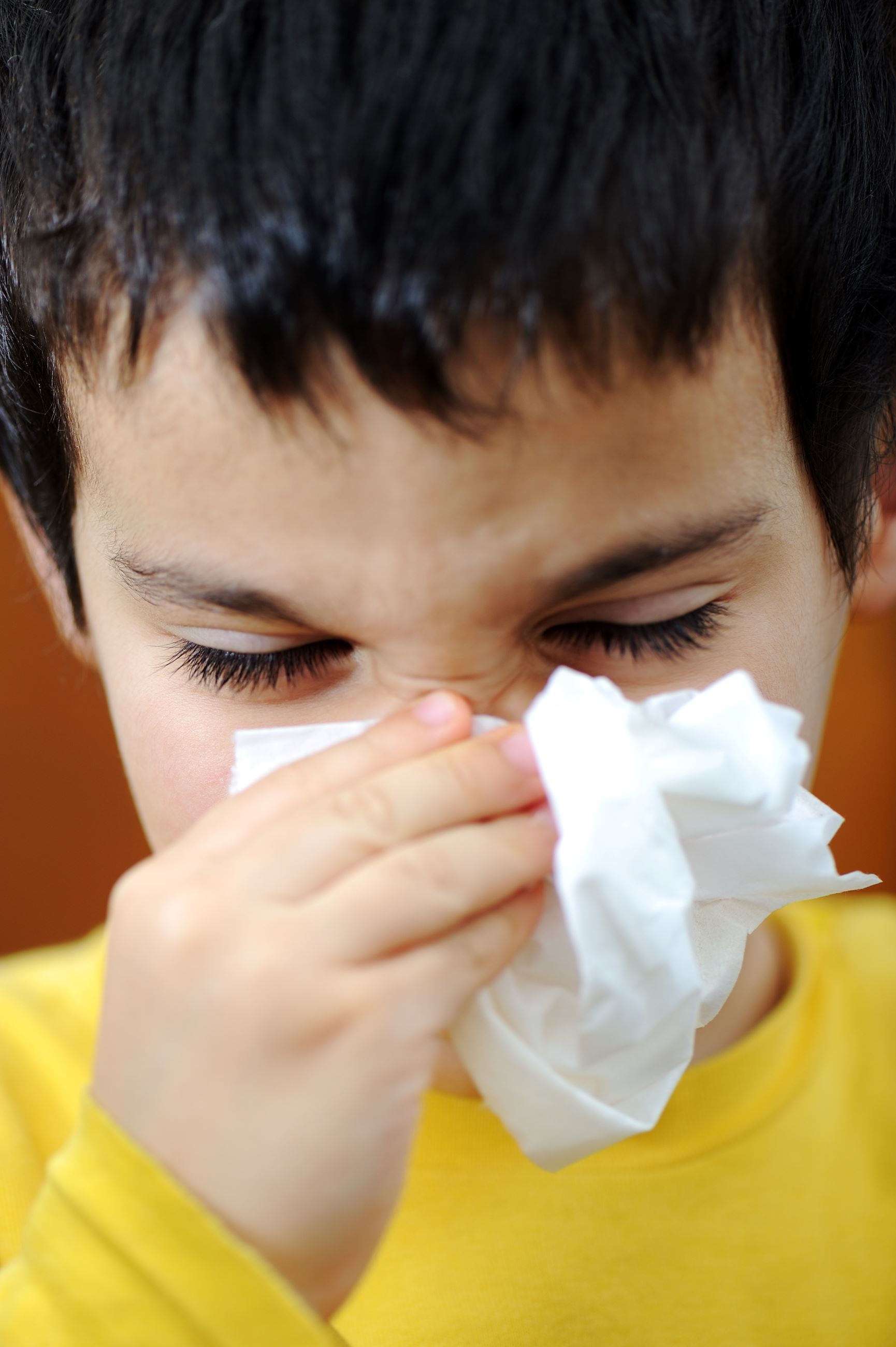 Boy sick with the flu blowing his nose